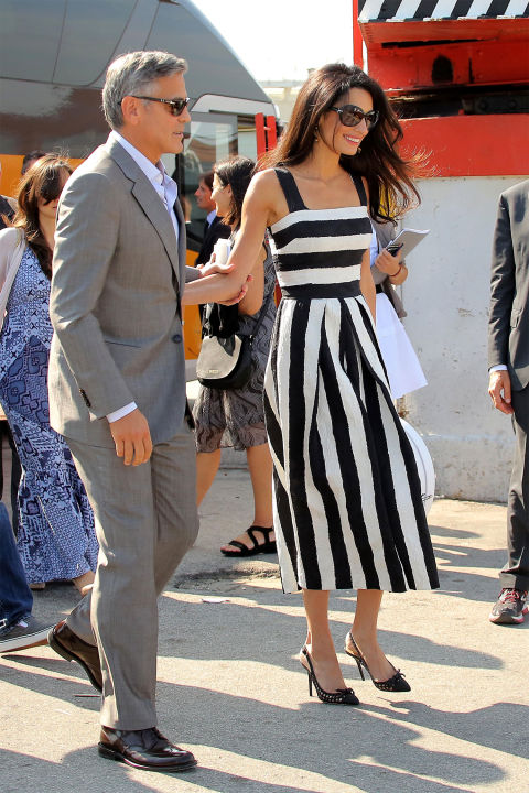 Looking wonderful in a white and black Dolce & Gabbana dress with competing horizontal and vertical stripes. She accessorized the look with Prada sunglasses and Dolce & Gabbana slingback heels.